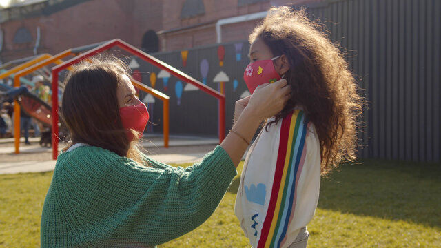 Side view of caucasian mother putting safety mask on african daughter face outdoors