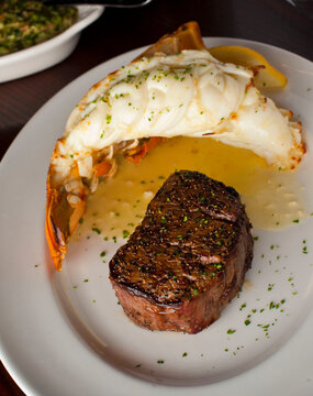 Surf 'n Turf, lobster tail and steak entree. Filet mignon topped with chanterelle mushrooms & Maine lobster tail topped w/ drawn butter served on white dinner plate. Classic steakhouse menu favorite.