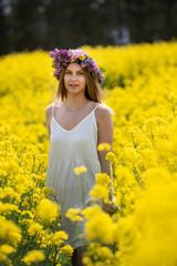 Obraz piękna kobieta na polu rzepaku cudowna słoneczna pogoda - fototapety do salonu