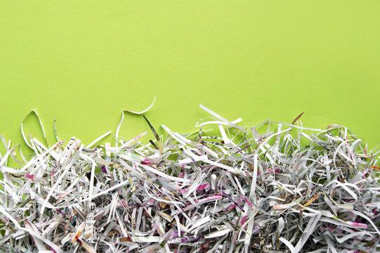 Shredded paper on light green background.