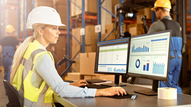Professional Female Worker Wearing Hard Hat Uses Computer with Inventory Status Checking and Delivery Software in the Retail Warehouse full of Shelves with Goods. Delivery, Distribution Center