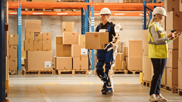 High-Tech Futuristic Warehouse: Worker Wearing Advanced Full Body Powered exoskeleton, Walks with Heavy Cardboard Box. Exosuit amplifies Human Performance, strength, Eliminates Work-Related Injuries