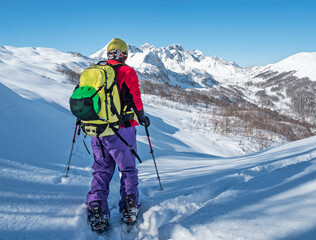 Active man ski touring on splitboard in mountains at snowy winter day