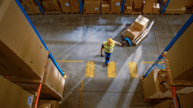 Top-Down View: Worker Moves Cardboard Boxes using Manual Pallet Truck, Walking between Rows of Shelves with Goods in Retail Warehouse. People Work in Product Distribution Logistics Center