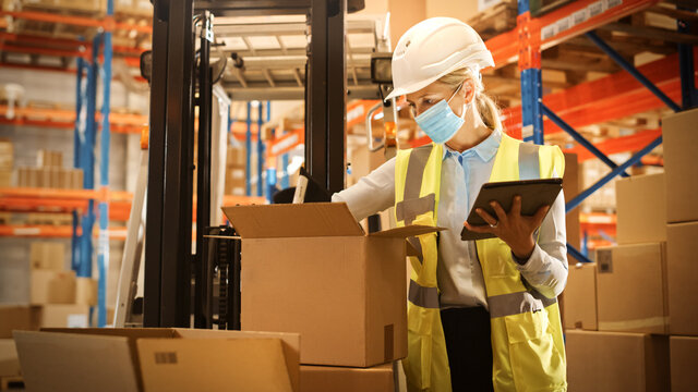 Female Warehouse Inventory Manager Wearing Face Mask for Safety, Using Digital Tablet Computer, Checking Cardboard Boxes. Delivery Distribution Center with Goods, Products Ready for Shipment