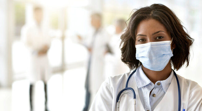 Woman doctor standing in hospital, wearing face mask