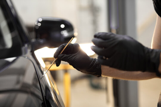 confident auto mechanic man using brush for painting a car, applying paint of black representative automobile after scratching