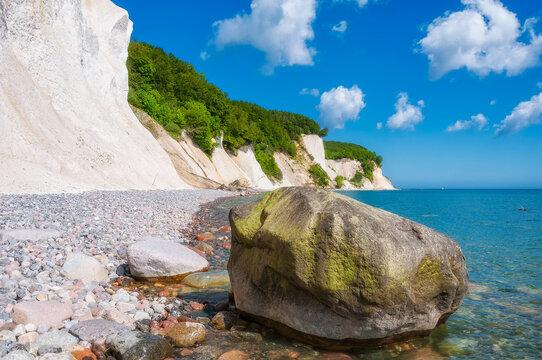 Felsbrocken vor der Küste Rügens mit den Kreidefelsen des Jasmund Nationalparks.
