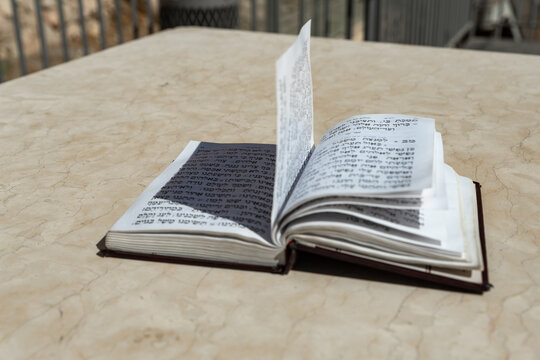 The open  holy book of Jews with the text of prayers in Hebrew - Tehelim, lies on a table near the Western Wall in the old city. of Jerusalem in Israel