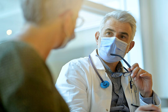 Doctor with face mask listening to patient in office, 19-ncov pandemic