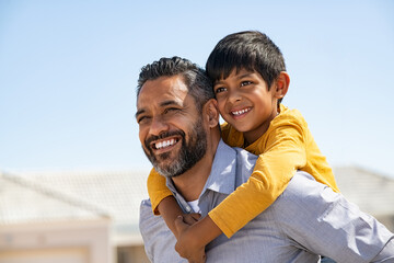 Happy smiling indian father giving son ride on back