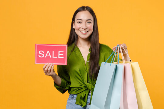 Smiling young brunette asian woman 20s in basic green shirt standing hold package bags with purchases after shopping sign with SALE title looking camera isolated on yellow background, studio portrait.