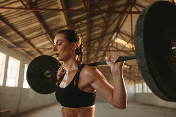 Fit woman exercising back squats with weights