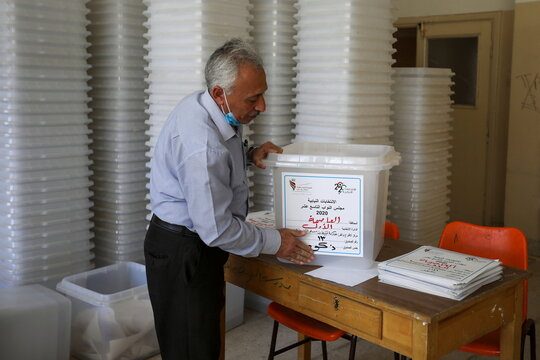 A Jordanian election official prepairs ballot boxes for the parliamentary elections which will be held on November 10, amid fears over rising number of the coronavirus disease (COVID-19) cases, at a vote counting center in Amman