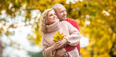 Leaf peeping by a couple in love in vibrant colorful nature