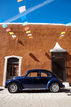 VW beetle in front of brown colonial building with flags on blue sky in Valladolid, Yucatan, Mexico