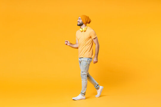 Full length side view of cheerful smiling funny young man 20s wearing basic casual t-shirt headphones hat walking going looking aside isolated on bright yellow colour background, studio portrait.