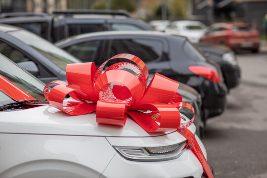 a white car with a big, red bow on the hood is on the street, an expensive gift, a new car as a gift, a gift car