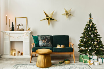 Stylish christmas living room interior with green sofa, white chimney, christmas tree and wreath,...