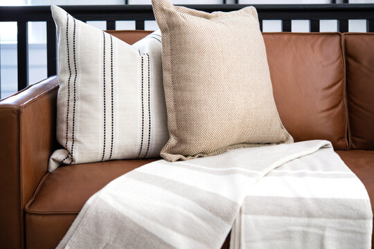 Livingroom couch with pillows and a throw