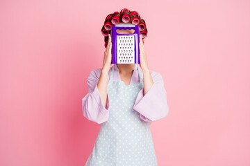 Photo of brown haired housewife hold grater cover face wear dotted apron isolated on shine pastel pink color background Wall mural