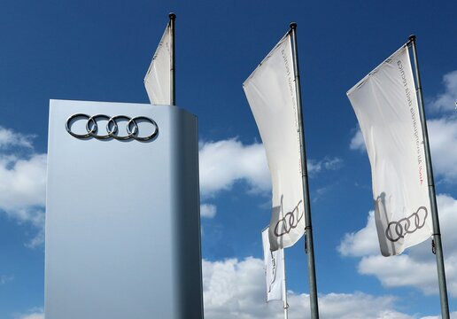 Udine, Italy. May 10, 2020. Audi logo and flags in the car dealership of the area, against a blue  sky  with clouds. It is the symbol of the   german luxury car manufacturer