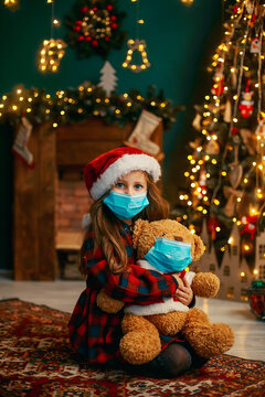 Portrait of cutel little child girl in medical mask playing with Taddy bear, New year holiday concept. Covid-19 concept.