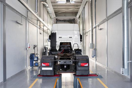 Truck in a car service for maintenance. Servicing and repairing trucks in a large garage. Car service, repair, diagnostics.