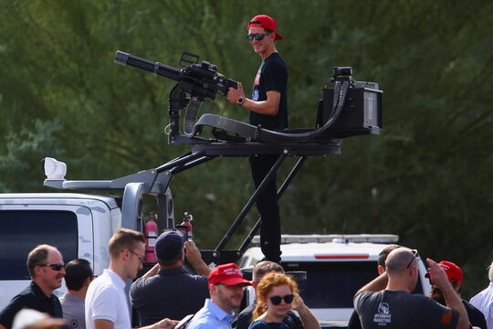A supporter checks a machine gun while is exhibited during a rally from Donald Trump Jr for U.S. President Donald Trump ahead of Election Day in Scottsdale, Arizona