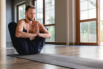Attractive caucasian flexible yogi man concentrating in lotus position in light roomy studio