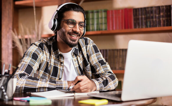 Positive Indian Student Guy At Laptop Learning Online At Home