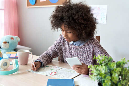 African american child kid girl holding phone distance learning class using mobile technology, watching online tutoring lesson, video calling in app making notes studying at home school in classroom.