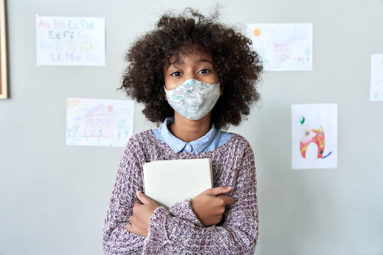 Cute small elementary reopen school pupil african american kid child girl wearing face mask holding book looking at camera standing in classroom. Children safety covid prevention protection concept.