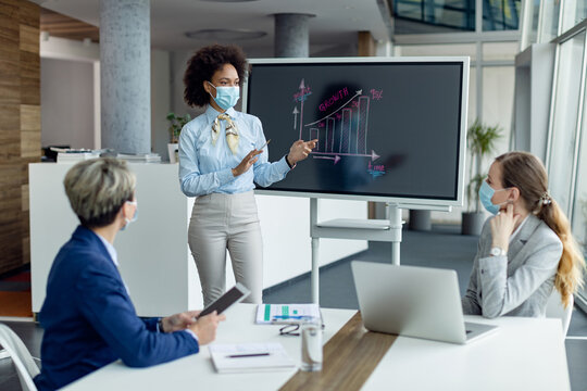 Black businesswoman with protective face mask giving a presentation in the office.