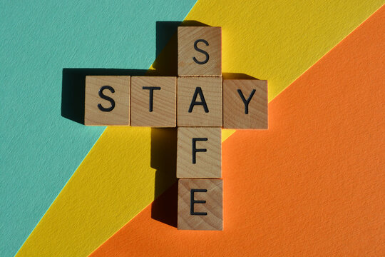Stay, Safe, words in wooden alphabet letters in crossword form isolated on colorful   background