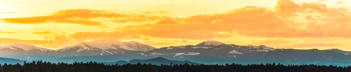 Styrian Lavanttaler Alps covered with snow in orange light of sunset.