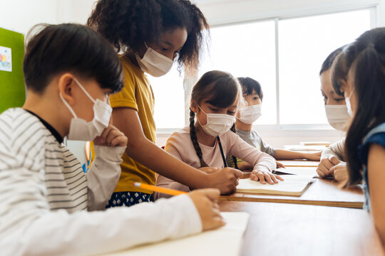 Young female teacher using an alcohol spray to disinfect student hands in classroom. Asian woman in face mask cleaning pupils' hands with hand sanitizer. School reopen after quarantine and lockdown.
