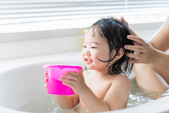 Cute Asian kid toddler having a bath cleaning bathing bath tub with mother, parenthood child hood love and care happy innocent having fun playing with water enjoying life moment white light background