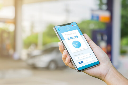 Online smart payment devices technology using mobile smartphone and checking marketing, merchant sales person selling product wireless digital money wireless transaction, hand gas station background