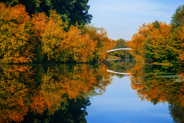 A picturesque bridge over a lake in an autumn park with colorful leaves that are reflected in the water