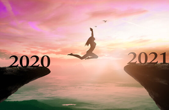 Success new year 2021 concept: Silhouette woman jump between 2020 and 2021 years with sunset background