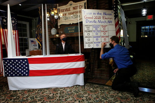 Tanner Tillotson writes on a board the results of ballots cast shortly after midnight for the U.S. presidential election at the Hale House at Balsams Hotel in the hamlet of Dixville Notch, New Hampshire