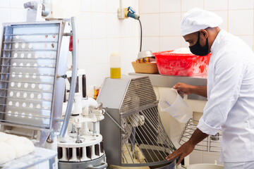 Professional hispanic baker controlling process of making bread dough in kneading machine in bakery