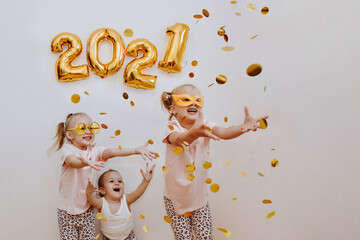 Three little girls are enjoying the flying golden confetti. Celebrating at home 2021. Concept for...