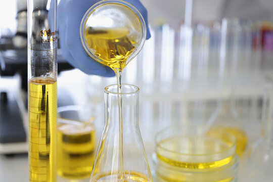 Hand in rubber glove pours yellow liquid into flask in chemical laboratory closeup. Pharmacological preparations production concept.
