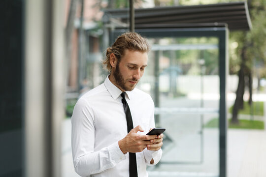 A curly-haired guy, in a white shirt and tie, at the bus stop looks at the phone while waiting for the bus. The concept of a mobile application for traffic in the city.