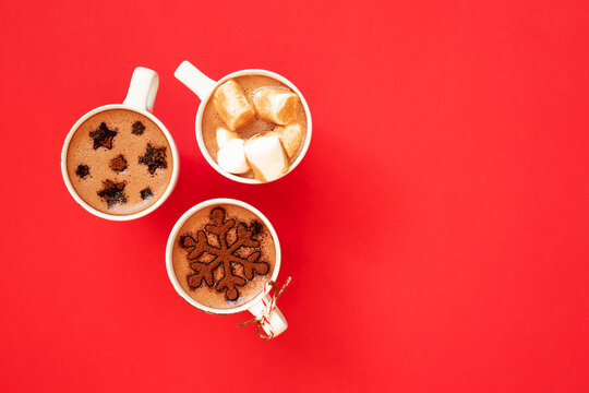 Hot chocolate with marshmallows and cocoa powder decor in white cups on red background
