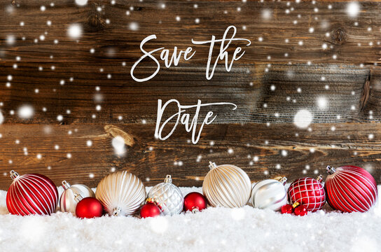 English Calligraphy Save The Date On Rustic Brown Wooden Backgroud. Red And White Festive Christmas Ball Ornament On Snow And Snowflakes