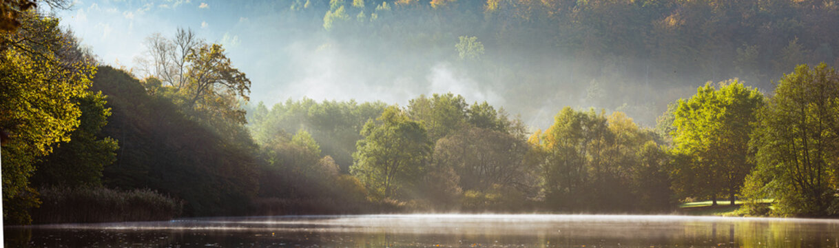 Panorama of foggy lake with Autumn foliage and tree reflections in Styria, Thal, Austria