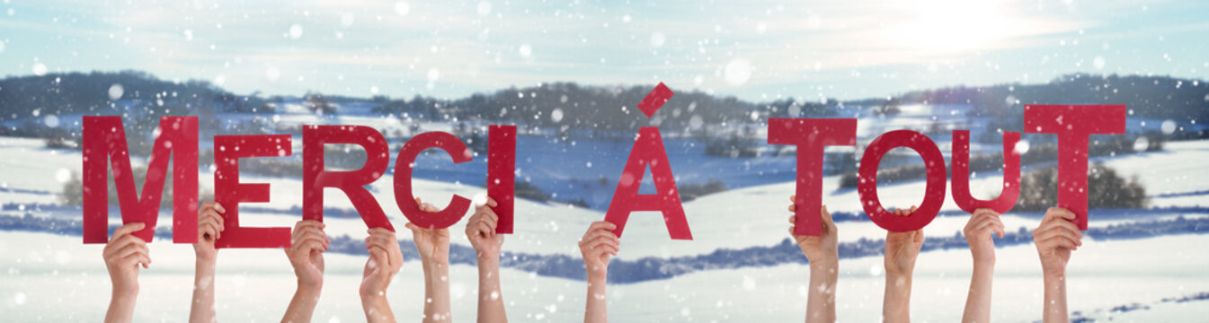 People Hands Holding Colorful French Word Merci A Tout Means Thank You All. Snowy Winter Background With Snowflakes
